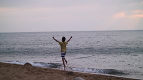 Happy little boy having fun and jumping in water at the beach in waves. Have fun stock images