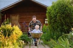 Happy little boy having fun in a wheelbarrow pushing by dad in domestic garden on warm sunny day royalty free stock photo