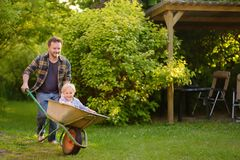 Happy little boy having fun in a wheelbarrow pushing by dad in domestic garden on warm sunny day stock photos