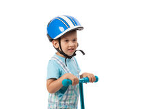 Happy little boy with helmet, playing with his scooter, isolated on white Royalty Free Stock Photo