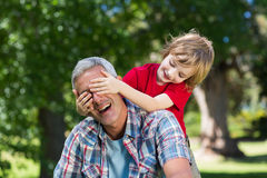 Happy little boy hiding his fatherss eyes with his hands Royalty Free Stock Photography