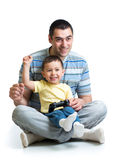 Happy little boy and his dad playing with a playst Royalty Free Stock Photos