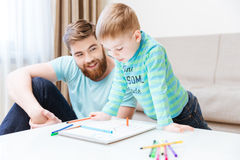Happy little boy and his father drawing together. At home Royalty Free Stock Image