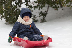 Happy little boy on his sled in winter snow Royalty Free Stock Photography