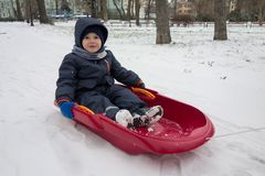 Happy little boy on his sled in winter snow Stock Photo