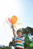 Happy little boy holding balloons Stock Photo