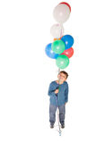 Happy little boy holding bunch of balloons Royalty Free Stock Image