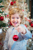 Happy little boy holding Christmas ball and decorating. Stock Photos