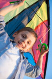 Happy little boy holding kite over his head and looking into the camera Stock Images