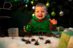 Happy little boy holds Christmas ball in hand, sits and smiles. stock image