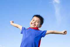 Happy little boy imitate superhero and open arms with blue sky. Background Royalty Free Stock Photography