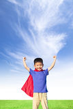 Happy little boy imitate superhero and open arms with blue sky. Cloud Stock Photography