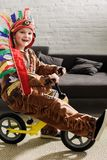 Happy little boy in indigenous costume on runbike playing. At home royalty free stock image