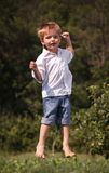 Happy little boy is jumping outdoor. Royalty Free Stock Image