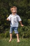 Happy little boy is jumping outdoor. Royalty Free Stock Photography