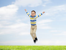 Happy little boy jumping over blue sky and grass. Happiness, childhood, freedom, movement and people concept - happy little boy jumping in air over blue sky and Stock Image