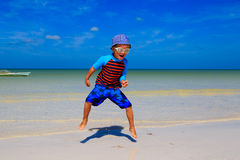 Happy little boy jumping on sand beach Royalty Free Stock Image