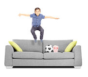 Happy little boy jumping on a sofa Stock Photos
