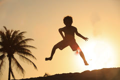 Happy little boy jumping at sunset beach stock photos