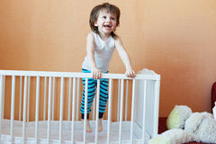 Happy little boy jumping in white bed Stock Photos