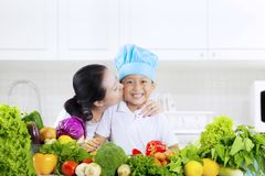 Child kissed by mother with vegetables in kitchen. Happy little boy kissed by his mother while wearing a cooking hat with vegetables in the kitchen stock image