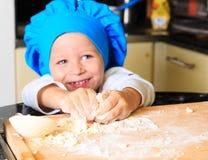 Happy little boy kneading dough Royalty Free Stock Image
