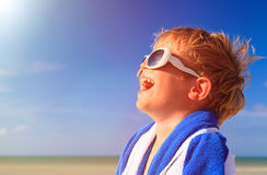 Happy little boy laugh wrapped in beach towel on Stock Photos