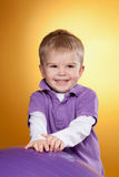 Happy little boy laughs near big violet ball Stock Image