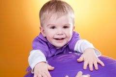 Happy little boy laughs near violet ball Royalty Free Stock Image