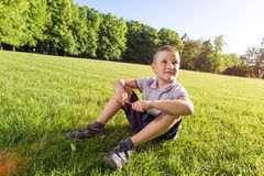 Happy little boy laying on the grass Stock Image