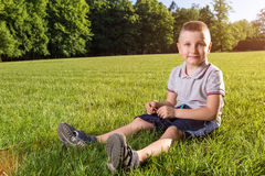 Happy little boy laying on the grass Royalty Free Stock Image