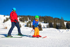 Happy little boy learning skiing with his father. During winter holidays in Alps Stock Photography
