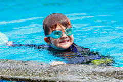 Happy little boy learning to swim in pool Stock Photography