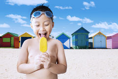 Happy little boy licking ice cream at shore Stock Photography