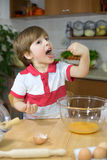 Happy Little Boy Licking Whisk with Whipped Eggs in the Kitchen Stock Photo