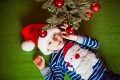 Happy little boy is lies near fir-tree. New Year's holidays.  in a striped T-shirt with Santa Claus Stock Images