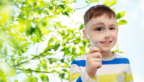 Happy little boy looking through magnifying glass Royalty Free Stock Images