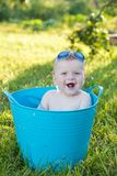 Happy little boy looking out from swimming pool. Cheerful little boy sits in a basin in from swimming pool Royalty Free Stock Photography