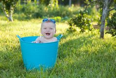 Happy little boy looking out from swimming pool. Cheerful little boy sits in a basin in from swimming pool Royalty Free Stock Image