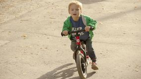 Happy little boy looks ahead and runs on a runbike stock photos