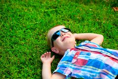 Happy little boy lying down resting on the green grass Stock Photo