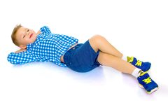 Happy little boy is lying on the floor in the studio. Happy little boy lies on the floor in the studio on a white background. The concept of a happy childhood Royalty Free Stock Images