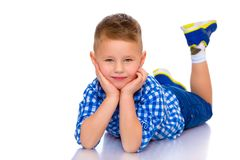 Happy little boy is lying on the floor in the studio. Happy little boy lies on the floor in the studio on a white background. The concept of a happy childhood Royalty Free Stock Photo
