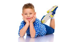 Happy little boy is lying on the floor in the studio. Happy little boy lies on the floor in the studio on a white background. The concept of a happy childhood Royalty Free Stock Photos