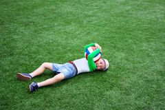 Happy little boy is lying on the football field with the ball stock photos