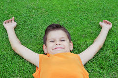 Happy little boy lying on green grass. Royalty Free Stock Photos