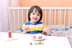 Happy little boy made lollipops of playdough and toothpicks at h Royalty Free Stock Image