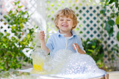 Happy little boy making experiment with colorful water and soap. Happy little boy making experiment with colorful soap bubbles and water, outdoors royalty free stock photos