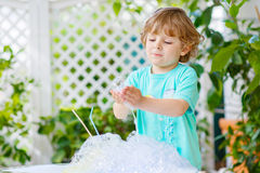 Happy little boy making experiment with colorful water and soap. Happy preschool child having fun and making experiment with colorful soap bubbles and water royalty free stock photos