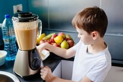 Happy little boy is making healthy fruit juice at home. Healthy eating Stock Images